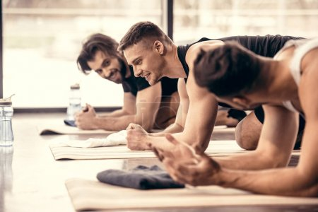 side view of smiling handsome sportsmen talking and simultaneously doing plank in gym