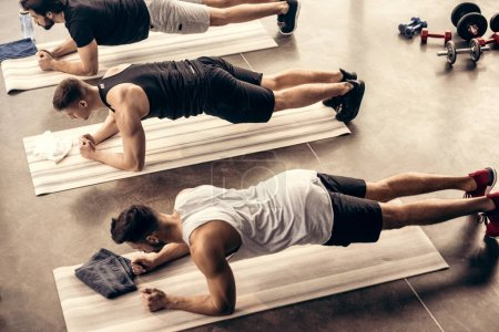 high angle view of muscular sportsmen simultaneously doing plank in gym