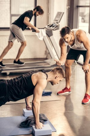 trainer counting while sportsman doing plank on yoga blocks in gym
