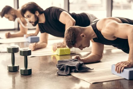 handsome sportsmen simultaneously doing plank and using blocks in gym