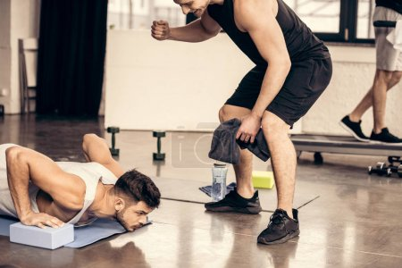 Photo for Trainer supporting sportsman doing plank on yoga blocks in gym - Royalty Free Image