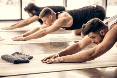 handsome sportsmen simultaneously stretching backs in gym