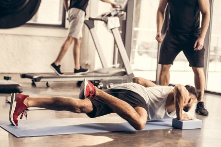 cropped image of trainer standing near sportsman doing plank on yoga blocks in gym