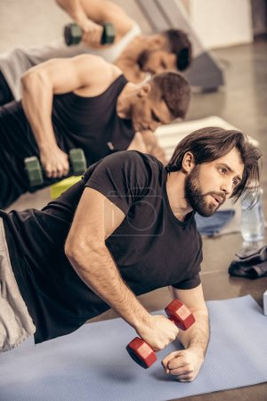 handsome sportsmen simultaneously training with dumbbells on floor in gym