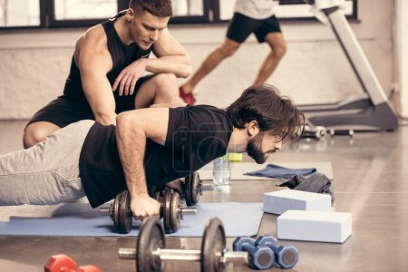 side view of handsome sportsman doing push ups on dumbbells in gym