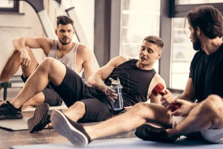 Photo for Handsome sportsmen resting on yoga mats after training in gym - Royalty Free Image