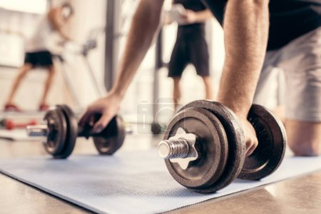 Photo for Cropped image of sportsman preparing doing push ups on dumbbells in gym - Royalty Free Image