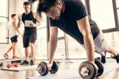 tired sportsman doing push ups on dumbbells in gym, trainer counting results