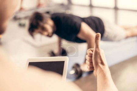 trainer holding tablet and showing thumb up to sportsman doing push ups on dumbbells in gym