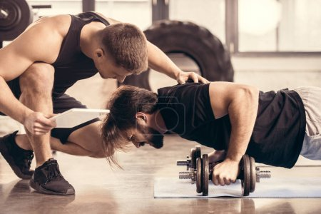 side view of trainer pushing sportsman doing push ups on dumbbells in gym
