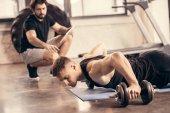 beau sportif faisant large push ups sur haltères dans la salle de gym