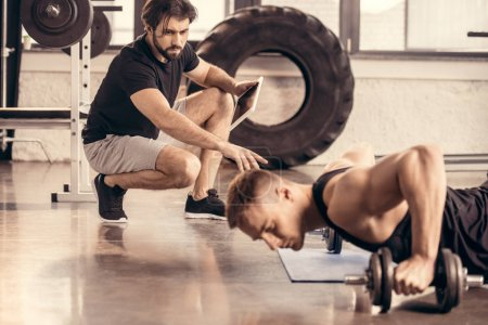 Photo for Handsome sportsman doing wide push ups on dumbbells in gym, trainer pointing on something - Royalty Free Image
