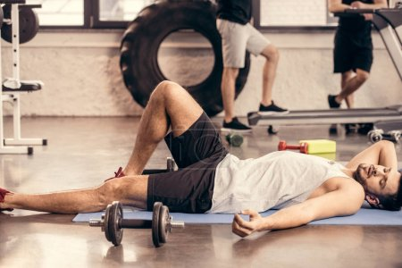 handsome tired sportsmen lying on yoga mat and resting in gym