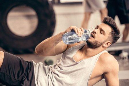 handsome sportsman drinking water in gym