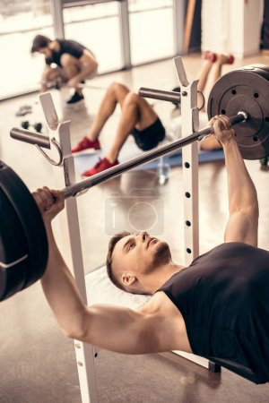 handsome sportsman lifting barbell in gym