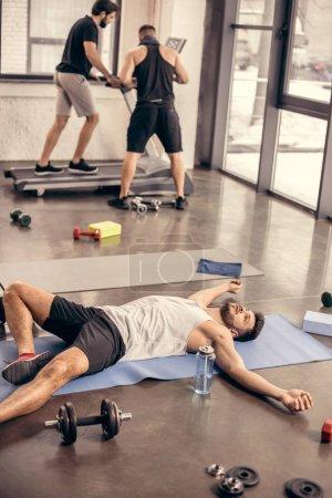 handsome tired sportsmen lying on yoga mat in gym