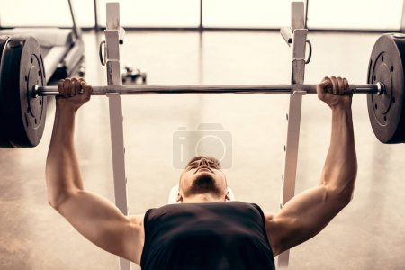handsome muscular sportsman lifting barbell in gym