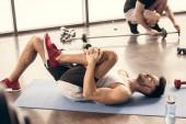 handsome sportsmen stretching legs on yoga mat in gym