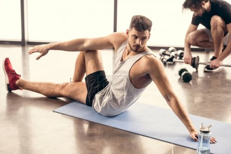 handsome sportsmen stretching on yoga mat in gym