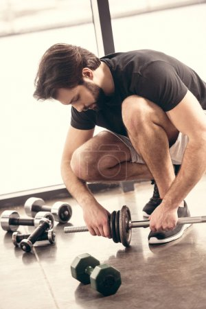 handsome sportsman putting weight plates on iron bar for training in gym