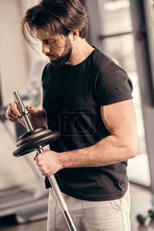 handsome sportsman fixing weight plates on iron bar for training in gym