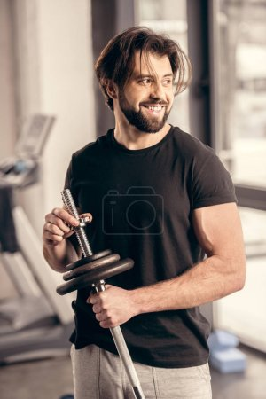 smiling handsome sportsman fixing weight plates on iron bar for training in gym