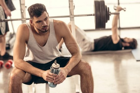Photo for Handsome sportsman resting with bottle of water on bench press in gym - Royalty Free Image