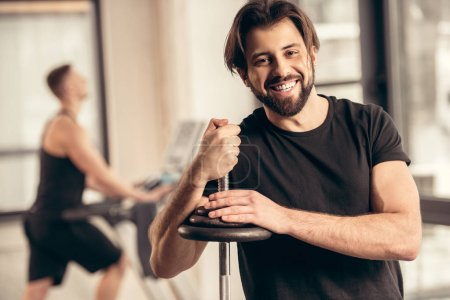 smiling sportsman leaning on iron bar with weight plates in gym