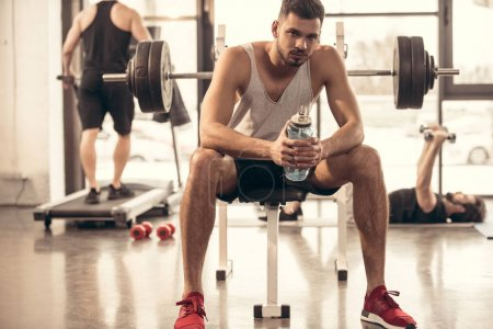 handsome sportsman sitting with bottle of water on bench press in gym