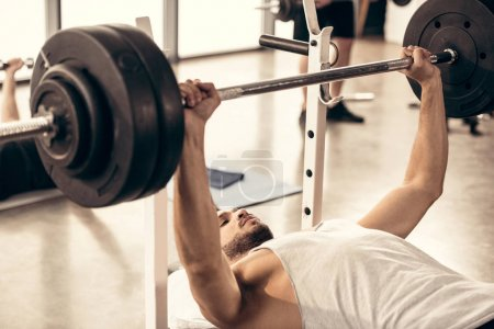 handsome sportsman lifting barbell with heavy weight plates in gym