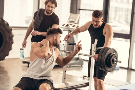 handsome sportsman having pain in neck and talking with friends in gym