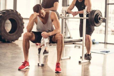 beau sportif fatigué, assis et au repos sur le banc de presse dans la salle de gym