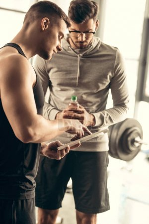 handsome trainer showing results of exercising on tablet to sportsman in gym