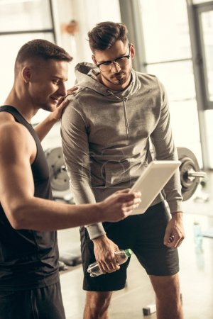 handsome trainer showing results of exercising on tablet to exhausted sportsman in gym