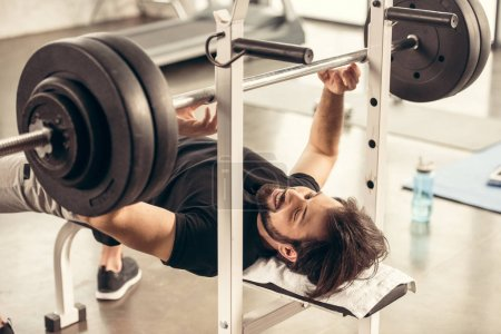 smiling handsome sportsman preparing lifting barbell on bench press in gym