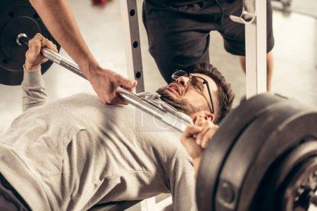 Foto de Recortar imagen de entrenador ayudando a deportista de levantamiento de barra con pesas en gimnasio - Imagen libre de derechos