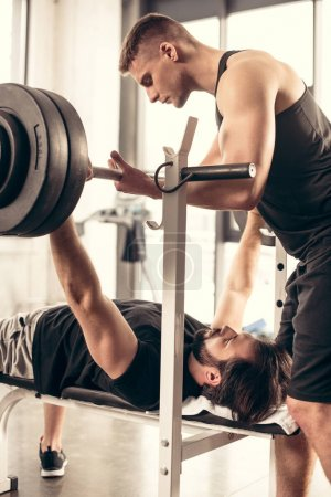 handsome trainer helping sportsman lifting barbell in gym