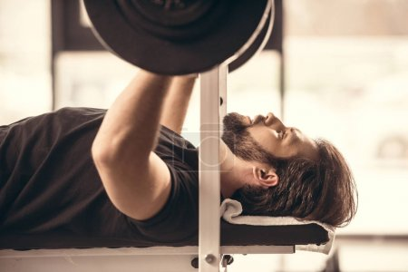 side view of handsome sportsman lifting barbell with weight plates in gym