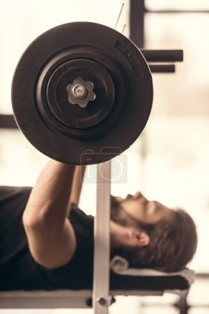 side view of handsome sportsman lifting barbell with weights in gym