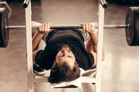 handsome sportsman exercising on bench press in gym