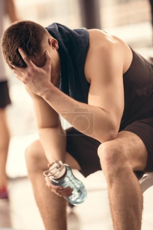 Photo for Tired sportsman holding bottle of water and resting in gym - Royalty Free Image