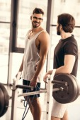 handsome smiling sportsmen looking at each other in gym
