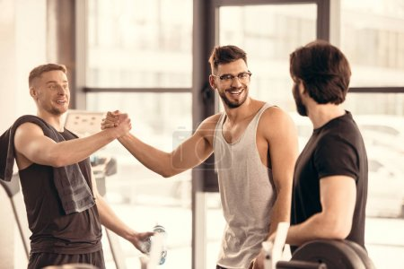 handsome smiling sportsmen greeting in gym