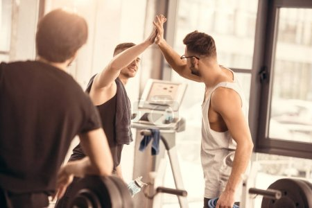 handsome sportsmen giving high five in gym