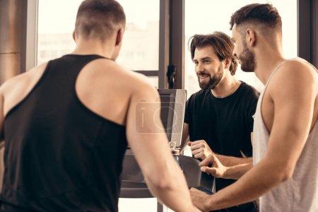 smiling handsome sportsmen near treadmill in gym