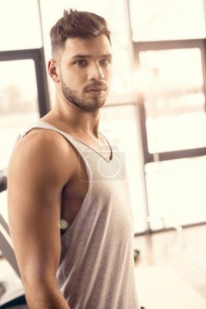 portrait of handsome sportsman looking at camera in gym