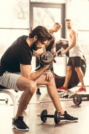 side view of handsome muscular man training with dumbbells in gym