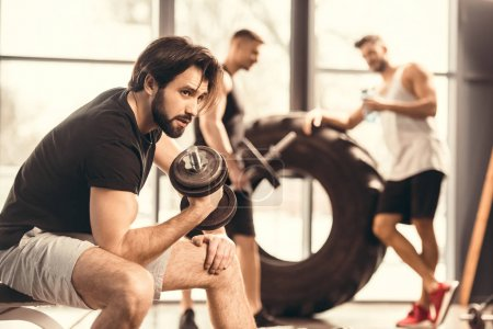side view of handsome young man lifting dumbbell and looking away in gym