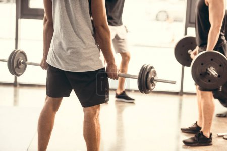 cropped shot of sporty young men in sportswear lifting barbells in gym