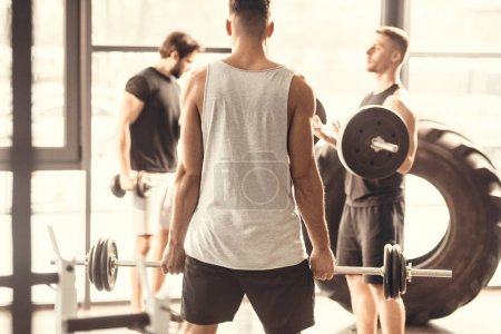 back view of muscular young man lifting barbell and looking at friends in gym